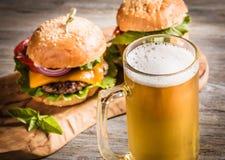 Mug of beer and hamburgers Royalty Free Stock Image