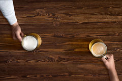 Mug of beer in hand on background of the wooden texture Royalty Free Stock Photos