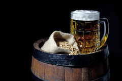 Mug of Beer and Jute Bag with Wheat on Barrel  on Black Royalty Free Stock Image