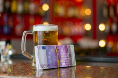 Mug of beer and money Stock Photo