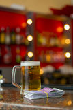 Mug of beer and money Stock Images