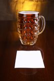 Mug of beer and note Royalty Free Stock Images