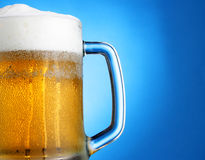 Mug of beer over blue. Mug of beer close-up with froth over blue background Royalty Free Stock Photo