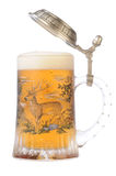 Mug of beer with path. Souvenir glass with the image of the wild nature, filled by beer, with the slightly opened cover Royalty Free Stock Photography