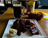 Mug of beer and plate of grilled pork ribs in Prague, Czech Republic. Mug of beer and plate of grilled pork ribs Prague, Czech Republic Stock Photo