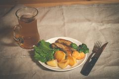 Mug of beer with plate of grilled sausages. And roasted potato on table Royalty Free Stock Photography