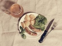 Mug of beer with plate of grilled sausages. Vintage style. Top view Royalty Free Stock Photos