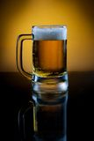 Mug of beer with reflection on table Stock Photography