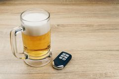 A mug of beer and a remote car key stock photography