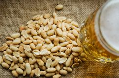 Mug with beer and salted peanuts on the table royalty free stock photo