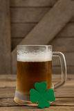 Mug of beer and shamrock for St Patricks Day. Glass of beer and shamrock for St Patricks Day on wooden table Stock Photo