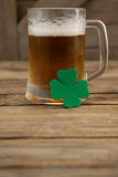 Mug of beer and shamrock for St Patricks Day. Glass of beer and shamrock for St Patricks Day on wooden table Stock Images