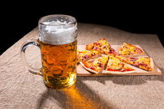 Mug of Beer and Slices of Pizza on Cutting Board Royalty Free Stock Image