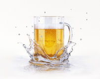 Mug of beer splashing on a water surface. Mug of beer, with condensation droplets, splashing on a water surface, creating a crown splash. On white background Royalty Free Stock Photography