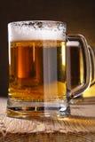 Mug of beer on table Royalty Free Stock Photos