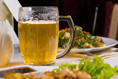 Mug of Beer on Table Amongst Plates of Food Royalty Free Stock Images