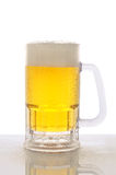 Mug of Beer on Wet Counter Top. A cold frosty mug of beer on a wet bar counter top with a white background. Vertical format with reflection Royalty Free Stock Photography