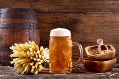 Mug of beer with wheat ears. On wooden background Stock Image
