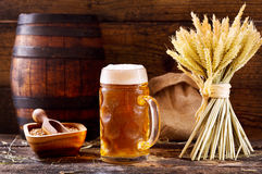 Mug of beer with wheat ears. On wooden background Royalty Free Stock Photography