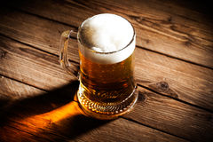 Mug of beer. On wooden background Stock Photography