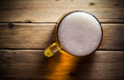 Mug of beer. On wooden background Royalty Free Stock Image
