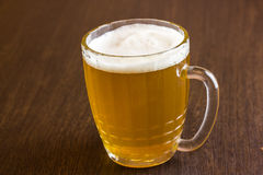 Mug of beer on wooden background Stock Photography