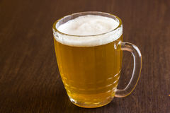 Mug of beer on wooden background Royalty Free Stock Photos