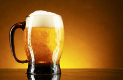 Mug of beer on a yellow Stock Photography