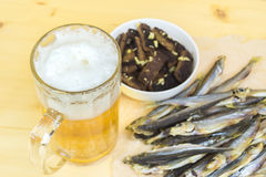Mug with a  beverage, crackers, dried fish on a wooden surface. Royalty Free Stock Photo