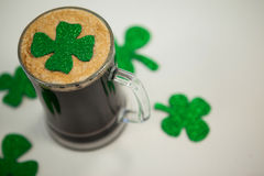Mug of black beer and shamrock for St Patricks Day Royalty Free Stock Photos