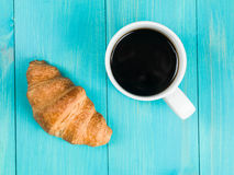 Mug of Black Coffee With A Single Breakfast Croissant Royalty Free Stock Image