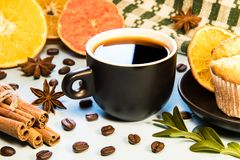 A mug of black coffee on a table with a cupcake napkin and cinnamon scattered coffee beans and sliced orange slices royalty free stock photos