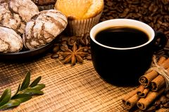 On a wooden table a mug of black coffee next to a plate of chocolate cookies sprinkled with powdered sugar, and on the background royalty free stock photos