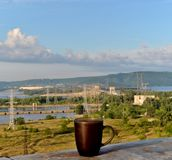 A mug of black tea on the background of the morning panorama of the Zhiguli Hydroelectric Station and the Zhiguli Mountains. royalty free stock images