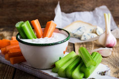Mug of blue cheese garlic dip sauce with celery and carrot stick. Mug of fresh blue cheese garlic dip sauce with celery and carrot sticks on wooden rustic table stock photos