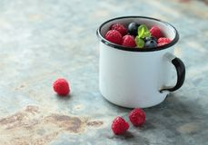 Mug with blueberries and raspberries. Tin mug with fresh fruits and mint leafs Royalty Free Stock Photos