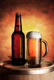 Mug and bottle of beer on a wooden barrel Stock Photography