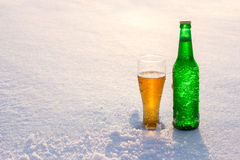 Mug and bottle of cold beer in the snow at sunset. Beautiful winter background. Outdoor recreation. Royalty Free Stock Images