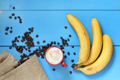 Red and yellow on blue. Mug with cappuccino, banana and coffee beans, on the table top view Stock Photo