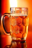 Mug of chilled beer with forth placed under the yellow colour. Evening sun light Royalty Free Stock Photo