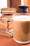 Mug of cocoa on a table nearby with old book and chocolate biscu Stock Photo