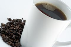 Mug of Coffee. Morning Americano surrounded by Beans Royalty Free Stock Images