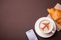Mug of coffee with an airplane on the foam. Morning coffee with croissant in flight. Smrtrfonom and cup of coffee Stock Image