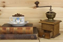Mug coffee beans and old books are on the shelf. Resting comfort over coffee and reading. Royalty Free Stock Photos
