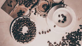 Mug with coffee beans. Coffee mug with coffee beans pass from each other, white mug, coffee beans, good mood, brown background Royalty Free Stock Images