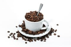 Mug with coffee beans on white background, concept photo. Closeup Royalty Free Stock Photography