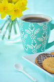 Mug of coffee with biscuits and daffodils Stock Images