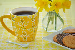 Mug of coffee with biscuits and daffodils Stock Image