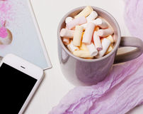 Mug coffee, cocoa with marshmallows and a phone stock photography