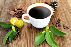 Mug with coffee and coffee grains on old wooden background Stock Photo